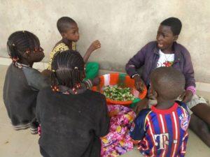 Kinder kochen mit geerntetem Gemüse